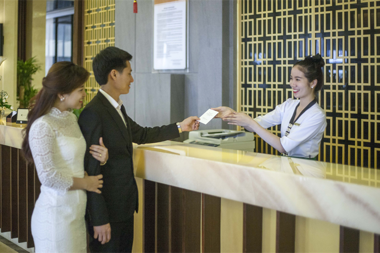Nhân viên lễ tân check-in cho khách
